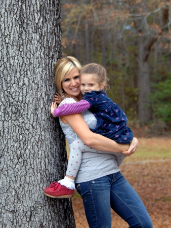 Play day outside includes hugs and affection and mother and daughter cuddle leaning against a tree on a Fall afternoon  photo