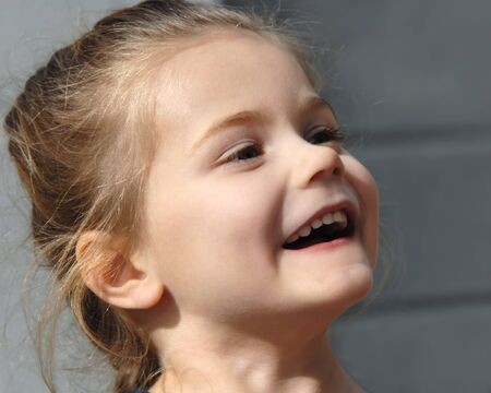 responds: Little girl laughing responds to situation   She has long hair and is looking up