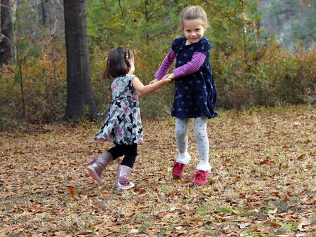 Two little girls hold hands and swing in circles   They are playing outdoor games in the Fall leaves  photo