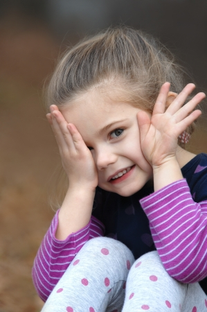 hands covering eyes: Small child is afraid to look as she peaps out from behind her hand   She is sitting outdoors in a colorful purple striped shirt