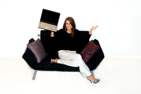 Beautiful young woman holds a computer in one hand and lifts an open palm in the other  She is sitting on a black futon  photo