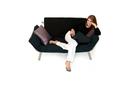composing: Attractive female spends her evening with her laptop computer   She is sitting on a black futon in an all white room   Stock Photo
