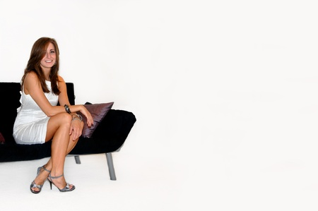 dressy: Beautiful young female dressed in a white dress, dressy heels and sitting on a black couch is smiling and radiant   She is sitting in the corner of an all white room