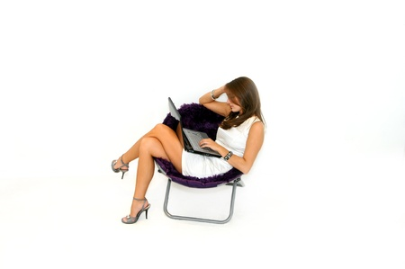 Beautiful female sits in mushroom chair with a laptop computer in her lap   She is wearing a white dress and heals and is working on her finances Stock Photo - 15044792