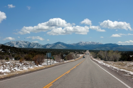Truck passes on a straight strentch while others enjoy the view of the Sandia Mountains just outside of Alberquerque, New Mexico.  Snow capped mountains loom just beyond the next hill. photo