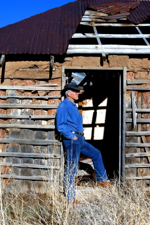 outdoorsman: Attractive male, dressed in denim and boots, leans against the door jam of an old adobe home outside of Alberquerque, New Mexico. Stock Photo