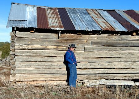 Man wearing jeans and a cowboy hat, leans against the wooden wall of an abandoned log cabin.  Building is outside of Alberquerque, New Mexico.   photo
