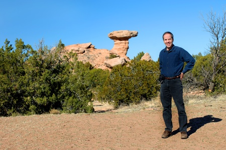 rock formation: Man visits famous landmark called Camel Rock outside of Santa Fe, New Mexico.  Camel Rock is a sandstone formation shaped like a sitting camel. Stock Photo