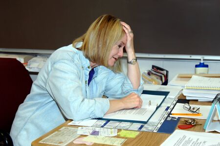 maestra ense�ando: Profesor de secundaria pone su cabeza en su mano y se inclina sobre la mesa en se�al de frustraci�n. Los grados de estr�s y pobre estudiante que se sienta el deseo de rendirse. Foto de archivo