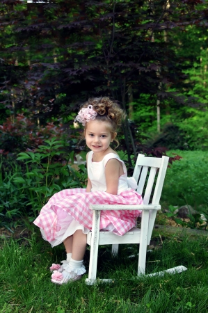 easter sunday: Little girl poses for picture on Easter Sunday morning.  She is wearing a pink and white gingham dress and curly ribbon hairbow.  She is sitting in a white wooden rocking shair and smiling. Stock Photo