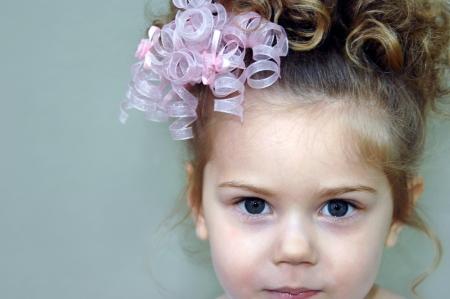 bow hair: Hermosa joven lleva rizos y un arco rizado pelo rosa. La imagen es de cerca de su cara. Foto de archivo
