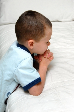 Small child kneels besides his bed and folds his hands in prayer   He is wearing a blue shirt and kneeling besides a white covered bed