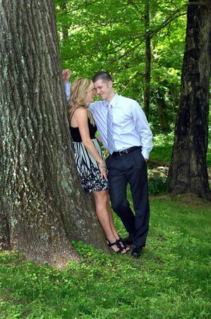 Beautiful couple laugh and share their dreams surrounded by natures beauty   They are leaning against a large tree trunk and are wearing dress clothing  photo