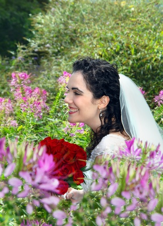Bride, holding red roses, is surrounded by pink flowers in an outdoor garden   She is smiling and laughing and joy radiates from her face  photo