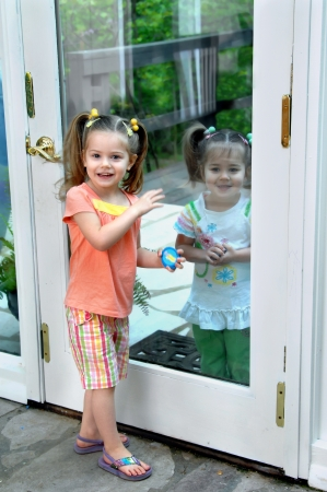 Two sisters act out  outside looking in  and  inside looking out    One sister is inside and the other on the outside of a glass patio door  Banque d'images