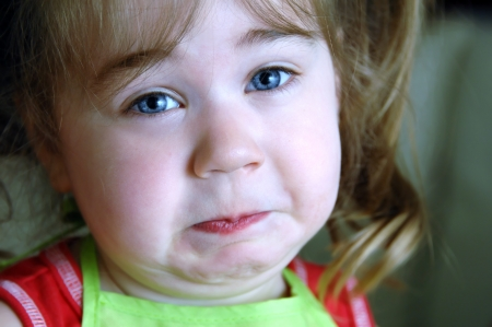Little girl helps mom cook broccoli and she wrinkles her face at the unpleasant odor   Closeup shows her pursed lips and wrinkled chin