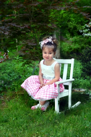Little girl poses on a white, wooden rocking chair   She is dressed in her Easter outfit and is smiling happily   Spring green surrounds her outdoors  photo