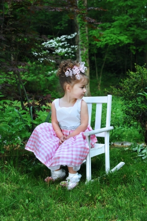 Sweet little girl enjoys Easter springtime dressed in her Sunday best   She is wearing a curly ribbon hairbow and a pink and white gingham dress  photo