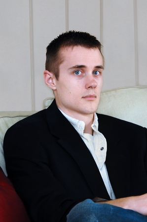 lost in thought: Young man sits on the sofa of his home.  He is wearing a navy sports coat and jeans.  His expression is solemn and his eyes stare straight ahead.
