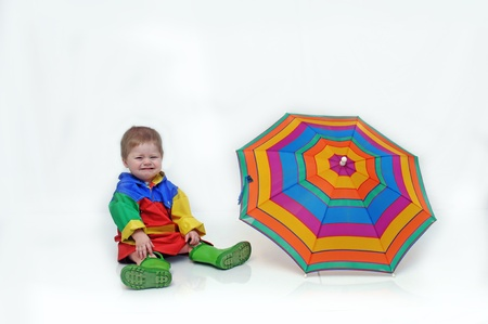 slicker: Baby boy, wearing a colorful slicker suit and rubber boots, is sitting besides an open umbrella and crying.