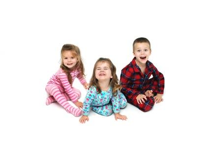 Drie kinderen reageren met opwinding op kerstochtend. Elke kamer heeft een andere reactie op hun gezichten. Er zijn drie, een jongen en twee meisjes. Stockfoto