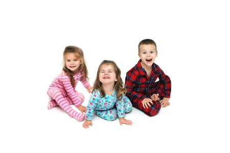Three children react with excitement on Christmas morning.  Each one has a different reaction on their faces.  There are three; one boy and two girls.