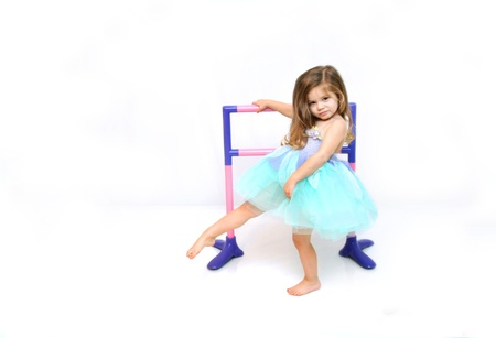 ballet bar: Beautiful little girl practices and stretches for her dance routine.  She is dressed in a ballerina costume of aqua and lilac. Stock Photo