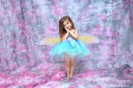 dressup: Ballerina wearing an aqua tutu and fairy wings stands in a room filled with pink and grey.  Her hands are folded against her cheek. Stock Photo