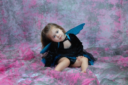 Adorable little girl is wearing a fairy costume and sitting in a room filled with pink and grey.  Her eyes are vivid blue and match her wings and skirt.  She is dreamy and serene. photo