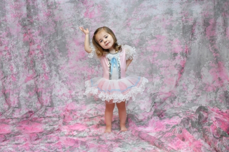 prima donna: Baby ballerina shows off her ballet moves.  She is dressed in a pink, blue and white tutu.  She has her arm raised and the other on her hip.