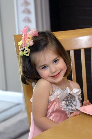 Little girl smiles happily at her ballerina birthday party   She is sitting at a wooden table holding a pink paper plate   She is wearing a pink costume Stock Photo - 15057412