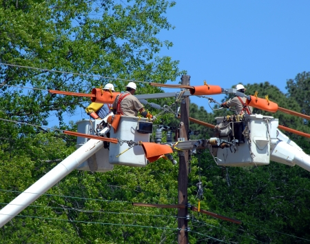 electric utility: Three buckets trucks lift linemen to top of electricity pole. Three repairmen combine knowledge and repair power outage.