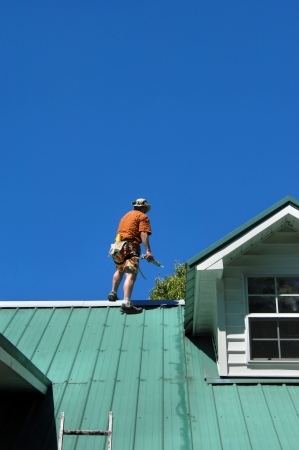 Young male makes repairs to his metal roof.  He is standing near the ridge holding a caulking gun.  A belt and rope gives him some measure of safety.  Blue sky frames him.
