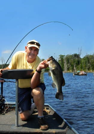 Angler kneels in his boat and holds his prize catch for the day, a five pound bass.  Other competitors look on with envy as this large bass was caught besides them.