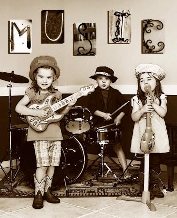 Drie broers en zussen doen alsof ze een muziekband Ze spelen instrumenten en een zingt de letters M, U, S, I, C is te vinden op de muur Jongste lid zijn zingt Stockfoto