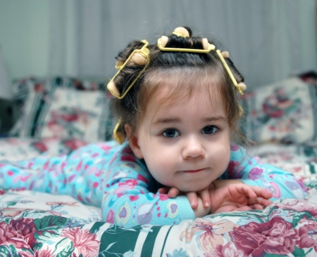 Toddler lays on her bed wearing pajamas and hair curlers   She is leaning her head on her hands and is lost in thought  photo