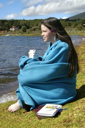 Blanket clad teenager sits besides lake in Mexico.  She is holding a cup of coffee and has her Bible and journal besides her.                             photo