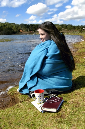 Teen spends some  alone time  on the beach at a lake side resort in Mexico   She is wrapped in a blanket and drinking a cup of coffee   Her Bible and journal lays besides her on the beach                                photo