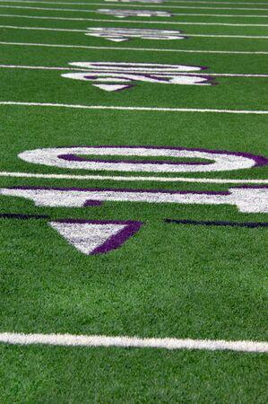 campo calcio: Linee segnare i metri di erba verde sul campo di football del liceo. I numeri dieci e venti sono illustrate in bianco e Purpe.