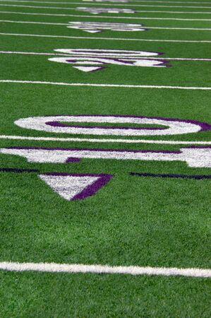 school football: Lines mark off yards of green turf on high school football field.  Numbers ten and twenty are outlined in white and purpe. Stock Photo