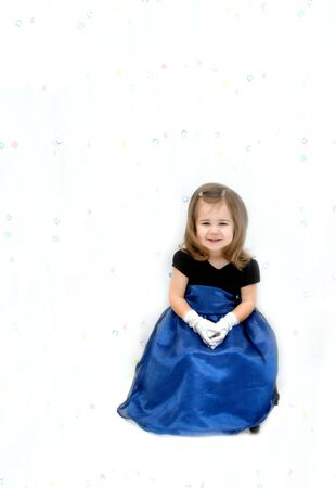 royal wedding: Little girl is wearing a royal blue gauze dress with velvet bodice.  She has long hair and is seated in front of a flower print curtain.