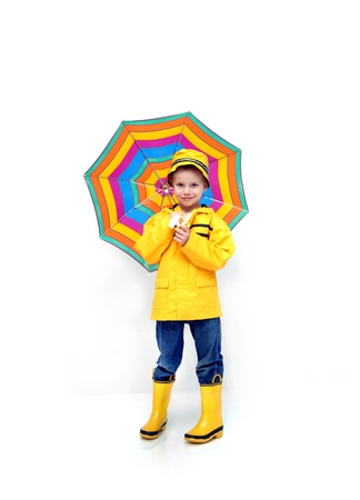 Little boy stands prepared for rain.  He is wearing a yellow raincoat and hat.  He is carrying a striped umbrella and has his jeans tucked into yellow, rubber galoshes. photo