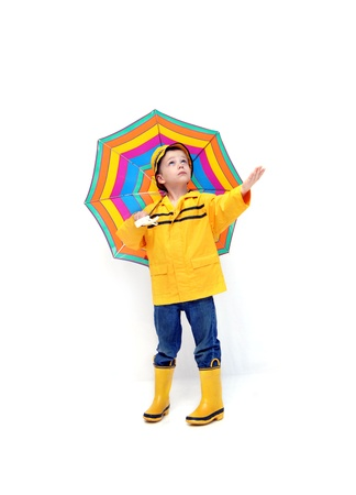 slicker: Young boy in yellow raincoat and rubber boots holds his hand out to check for rain.  He is holding a colorful striped umbrella.