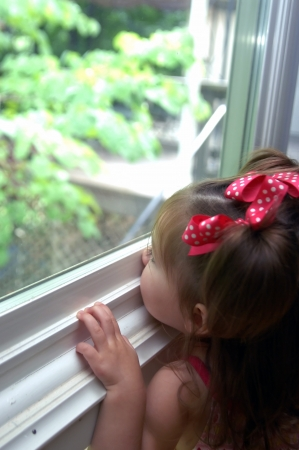 Toddler stretches to look outside her window   Her nose is pressed against the window seal and her mind is busy absorbing the world outside