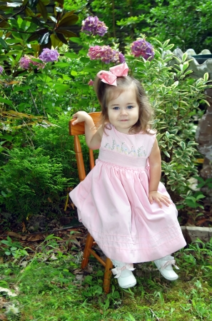 Easter Sunday morning is exciting for a little girl.  This one is dressed in pink with shoes tied with pink satin ribbon.  She is posing on a wooden chair set in the garden.  Hydrangea bloom behind her. photo