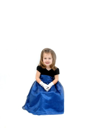 velvet dress: Little girl is wearing a royal blue gauze dress with velvet bodice.  She has long hair and is seated in an all white room.