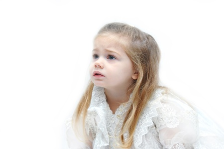 Little girl dressed in elegant and lacy gown looks upward with a concerned look on her face. Stock Photo - 15088731