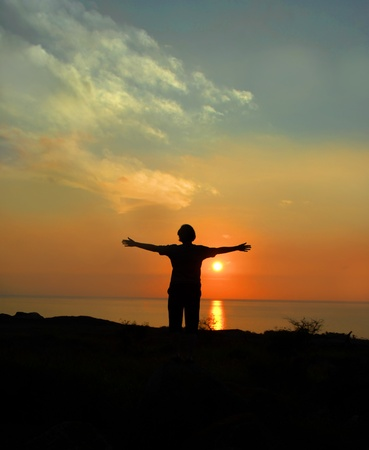 Visitor stands with arms wide saying goodbye to the Big Island of Hawaii.  The sun is setting ending the day as her trip is also ending.