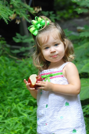 Little girl holds an apple that she is eating Stock Photo - 15088734