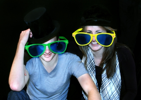 oversized: Young couple clown around with hats and oversized sunglasses.  They are both smiling and the man is tipping his top hat.
